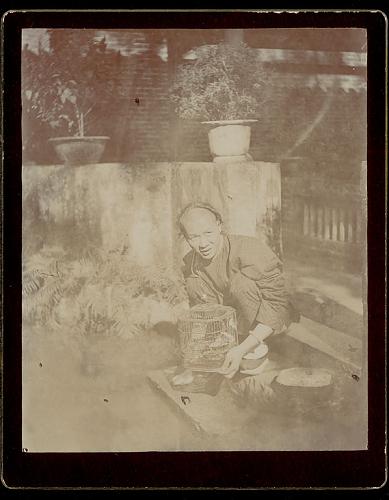 Mulher com cabaia e gaiola com pássaro num jardim, Macau 1896