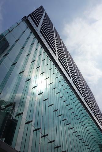 "Shimbashi_9 新橋で撮影した高層ビルディングの写真。 ""汐留住友ビル""。 直下から見上げる角度で撮影。 下層部分は緑色掛かったガラス張り。 ガラス張りの下層部分の上から下まで連なった垂直なガラス板が左端から右端まで等間隔に突き出ている。"