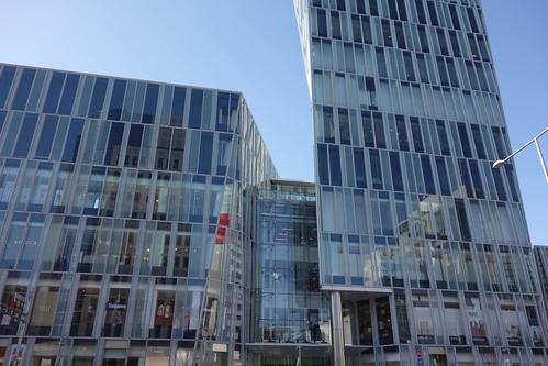"""Aoyama_1 青山通りの """"Ao"""" のビルディングを撮影した写真。 全面ガラス張りで3次元ジオメトリックな外観をしている。"""
