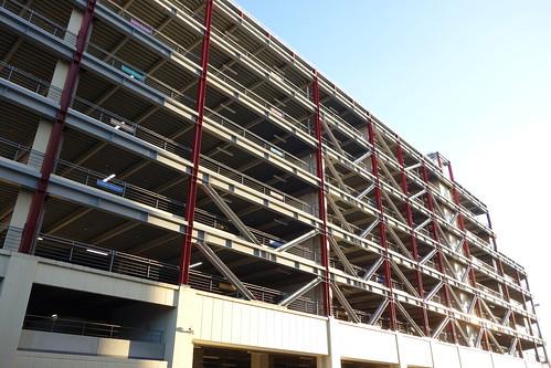 Kounosu_1 埼玉県鴻巣市にある立体駐車場の写真。 鉄骨のトラス構造である。 縦の鉄骨の柱はガーネット色である。 西日を掠めている。