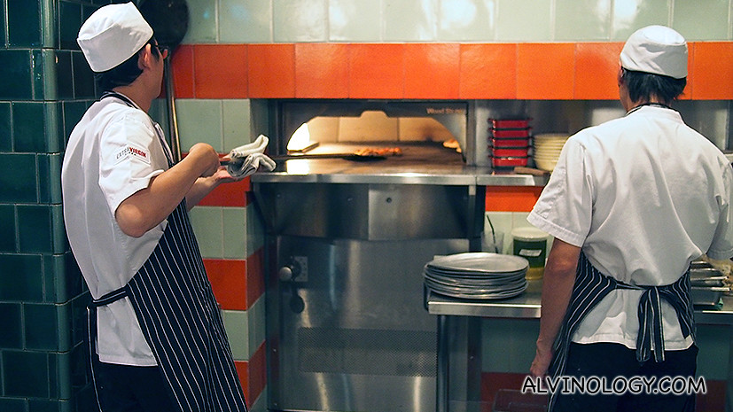 Sliding a freshly-topped pizza into the woodstone oven