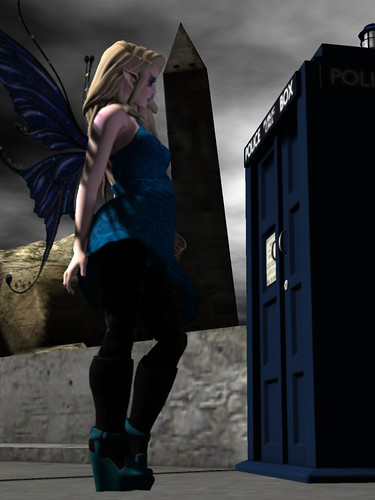 Image Description: A woman in profile wearing a blue dress, facing a TARDIS, with a tilted Washington Monument in the background.