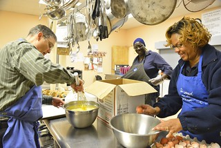 William Boeh, Kym Smith (center) and Traci Whitfield, civilian employees for the Coast Guard 5th District, cook breakfast at Oasis Social Ministry's kitchen in Portsmouth, Va., Monday, Nov. 17, 2014. Coast Guard members from throughout the Hampton Roads region volunteer to work at similar breakfasts approximately eight times each year. U.S. Coast Guard photograph by Petty Officer 3rd Class Nate Littlejohn