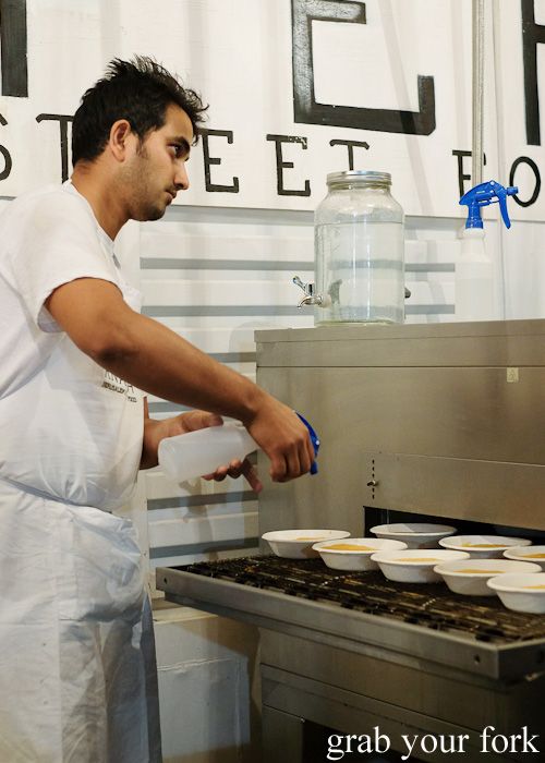 Spraying water onto the knafeh before they are grilled at Knafeh, North Strathfield