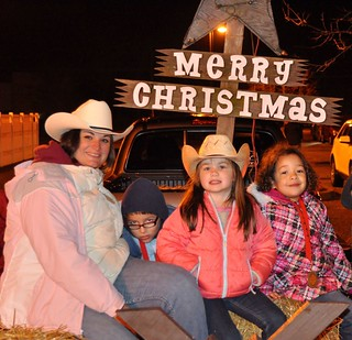 Petty Officer 1st Class Danielle Wnek sits with children during a Christmas parade in Cape May, N.J., Dec. 9, 2014. Wnek leads a Cloverbuds group to help children build foundations for confident and fulfilling lives. (U.S. Coast Guard photo)