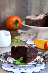 Piece of a chocolate cake with persimmon.