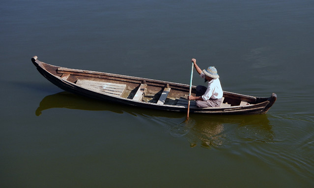 Boat going by U Bein Bridge in Mandalay, Myanmar