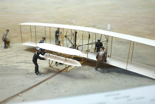 Shown here is a miniature replica of the Wright Flyer along with the Life-Saving surfmen who assisted.