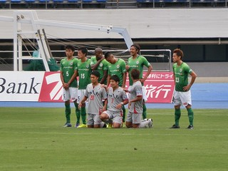 ロアッソ熊本のフリーキック。壁の前に立つ熊本の選手は膝立ちのため、さながら記念撮影の様。