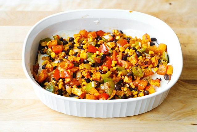 Spread roasted veggies (green bell pepper, red bell pepper, black beans, corn, onions) over the tortillas - Mexican enchilada casserole bake