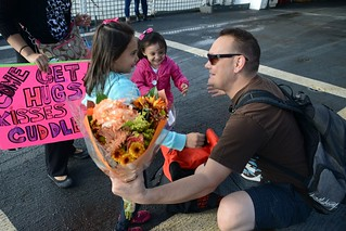 Petty Officer 2nd Class James Chavez, a machinery technician assigned to the Coast Guard Cutter Stratton, embraces his daughters at Coast Guard Island in Alameda, Calif., Nov. 28, 2014, after returning home from a 140-day deployment. Stratton and the cutter's 145-person crew provide the mission flexibility necessary to conduct counter-narcotics, homeland security, and alien migrant interdiction operations, domestic fisheries protection, search and rescue, and other Coast Guard missions at great distances from shore keeping threats far from the U.S. mainland. (Coast Guard photo by Petty Officer 3rd Class Loumania Stewart)