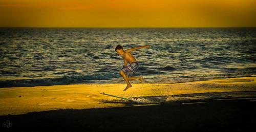 boy jumping unitedstates florida flash running sarasota runner skimboarding siestakey siestabeach fav10 aunset skimmerboard