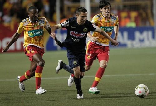 Paul Aguilar (centro) del América, disputa el balón con Edder Nelson (izquierda) del Herediano de Costa Rica durante el partido celebrado este martes. Foto Reuters