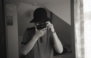 reflected self-portrait with Ricoh FF-3 AF camera and black hat