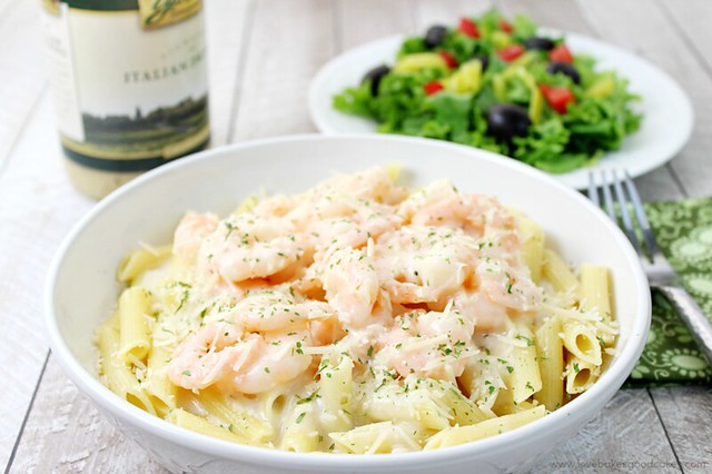 Parmesan Italian Shrimp with Pasta in a bowl with a plate of green salad and a fork.