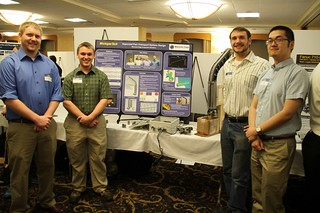 Improved Parts Transportation System Team posing with poster