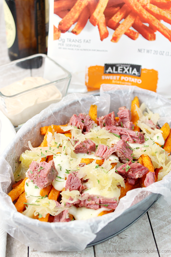 "Sweet potato fries topped with plenty of freshly chopped corned beef, melty Swiss Cheese sauce and tangy sauerkraut! Serve it with a homemade Russian Dressing for a meal that will make your taste buds say ""wow!"" #SpringIntoFlavor #Ad"