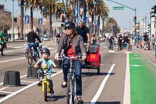 22365 Mother and son in two-way protected bike lane followed by pedicab