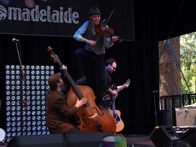 Gordie plays violin while standing on top of the double bass, tipped on its side and supported by the musician playing it.