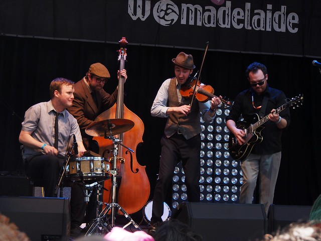 All four members of 'Gordie MacKeeman and his Rhythm Boys,' gathered close and playing drum, double bass, violin and guitar