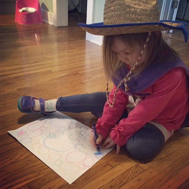 "She drew a bunch of ""Easter eggs"" and now she's coloring them in (while wearing her cape and cowgirl hat, because why not?)"