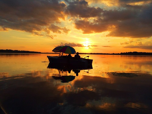 light sunset reflection clouds river boat fishing silhouettes