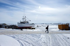 A man walks along a snow-covered road next to a frozen bay as U.S. Secretary of State John Kerry visits Iqaluit, Canada, just below the Arctic Circle, on April 24, 2015, for meetings of the Arctic Council, whose chairmanship the United States will assume the next two years. [State Department Photo/Public Domain]