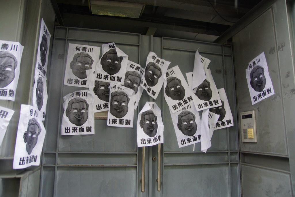 Hydis工人們將印有何壽川臉孔的標語挑滿住宅圍牆。(攝影:王顥中)