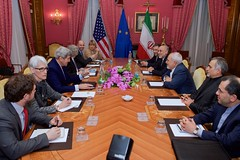 U.S. Secretary of State John Kerry - flanked by Under Secretary of State for Political Affairs Wendy Sherman, U.S. Energy Secretary Dr. Ernest Moniz, National Security Council Senior Director for Iran, Iraq, Syria and the Gulf States Robert Malley, and European Union Deputy Secretary General Helga Schmid - sits across from Iranian Foreign Minister Javad Zarif, Dr. Ali Akbar Salehi, the Vice President of Iran for Atomic Energy and President of the Atomic Energy Organization of Iran, and other advisers on March 28, 2015, in Lausanne, Switzerland, before resuming negotiations about the future of Iran's nuclear program. [State Department Photo / Public Domain]