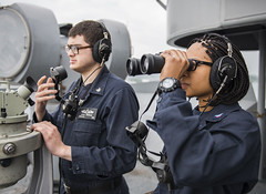 Operations Specialist 3rd Class Meagan Turner scans the horizon while standing lookout watch as Quartermaster 3rd Class Chris Rexrode stands by to relay the ship's position to the navigation bridge aboard the USS Ronald Reagan (CVN 76). (U.S. Navy/MCSN Jamaal Liddell)