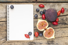 Fresh wild berries and figs with blank notebook on…