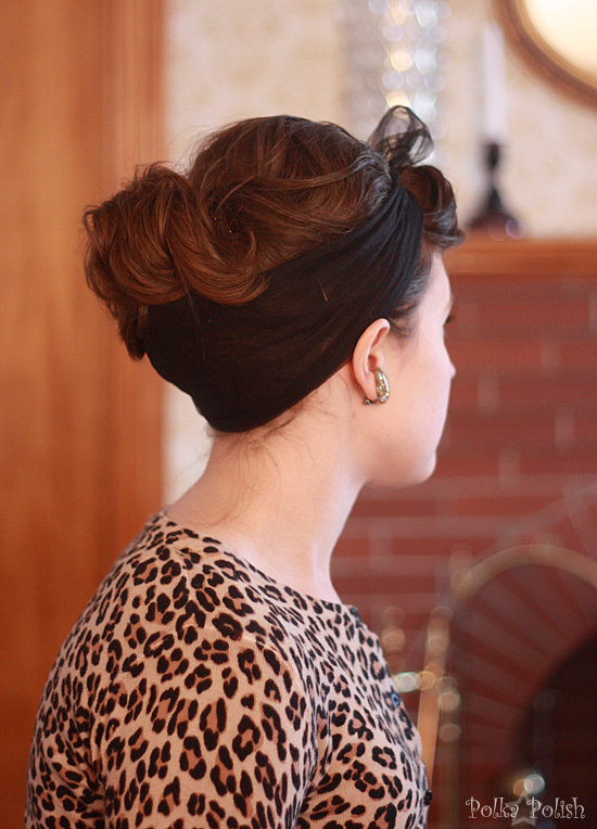 Leopard print sweater and a messy  boufant hairdo