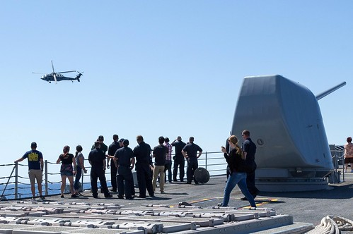 San Diego, CA -- Guests onboard USS LAKE CHAMPLAIN (CG 57) watch an SH-60S flight demonstration from the forecastle during the Friends and Family Day Cruise.