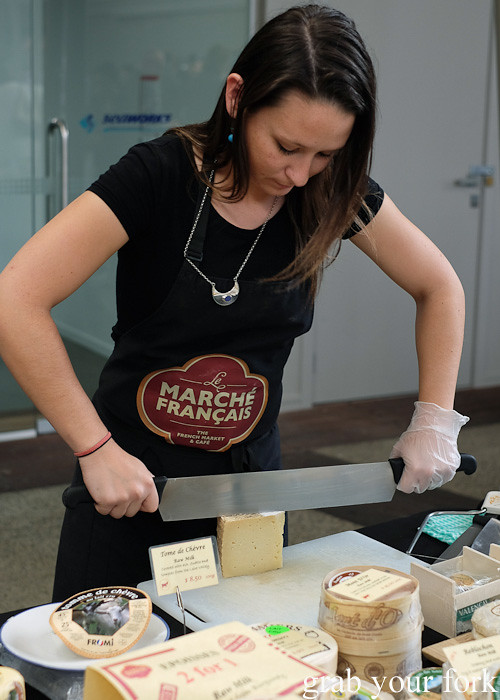 Cheesemonger at Le Marche Francais selling French cheeses at City Market, Wellington