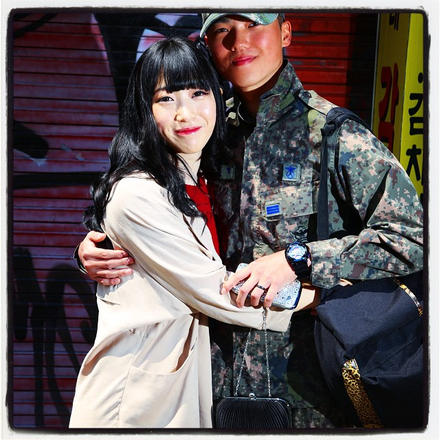 He did his compulsory military service after his freshmen year. She's a Chinese university student in a Korean university. He was holding her purse before she reclaimed her accessory item for the shoot. An interesting story-in-a-picture here.