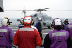 Sailors from the damage control and refueling teams aboard the U.S. 7th Fleet flagship USS Blue Ridge (LCC 19) observe an MH-60S Seahawk from Helicopter Sea Combat Squadron (HSC) 12 during flight operations, March 14. (U.S. Navy/MC3 Samuel Weldin)