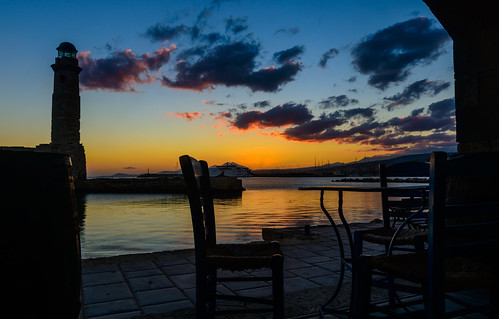 rethymno crete harbour sunrise port lighthouse sea golden table chairs
