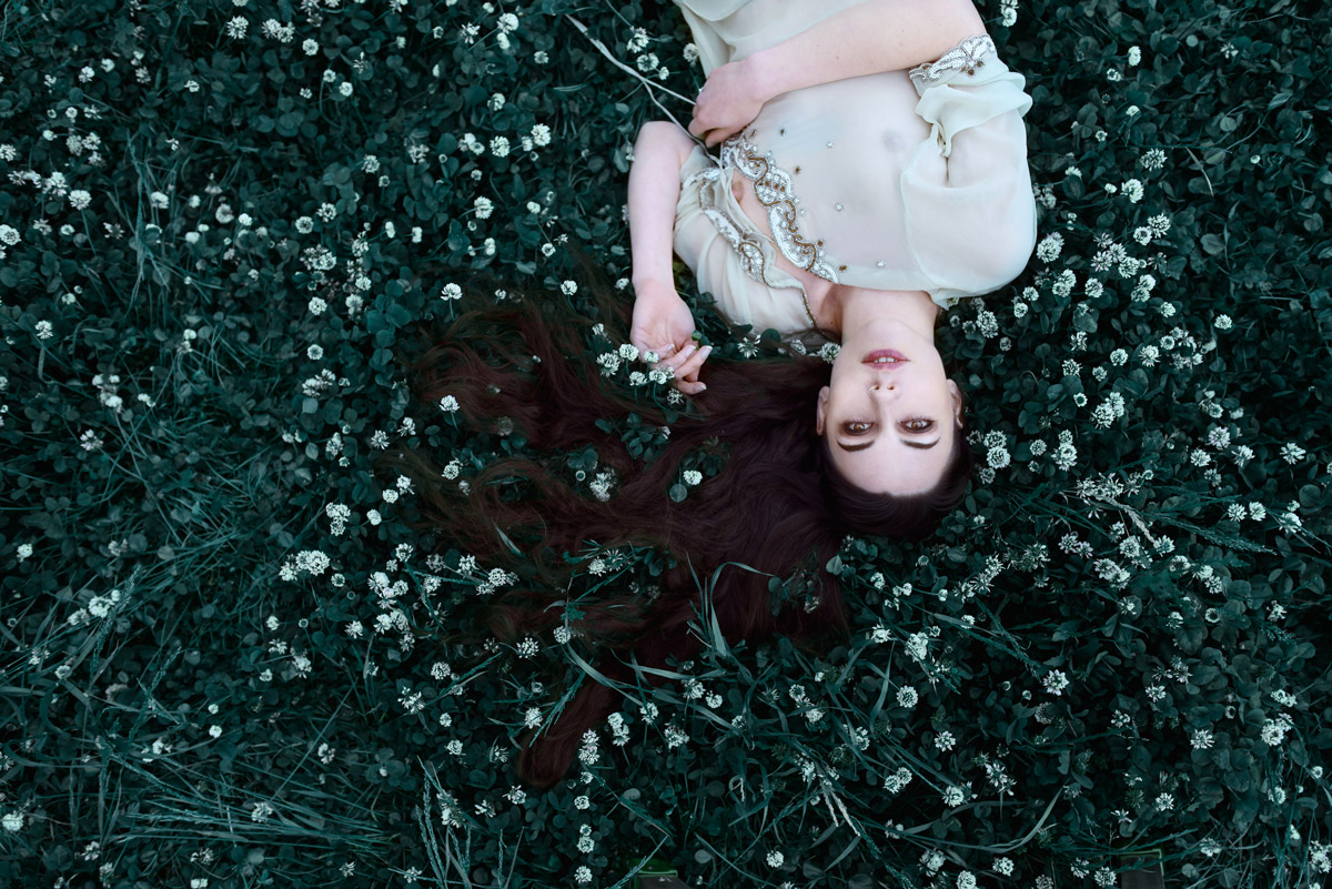 Gestalta photographed by Akiomi Kuroda. Girl with long black hair lying in deep green grass.