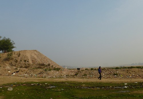 A man walks past a huge mountain of debris dumped on the river bed