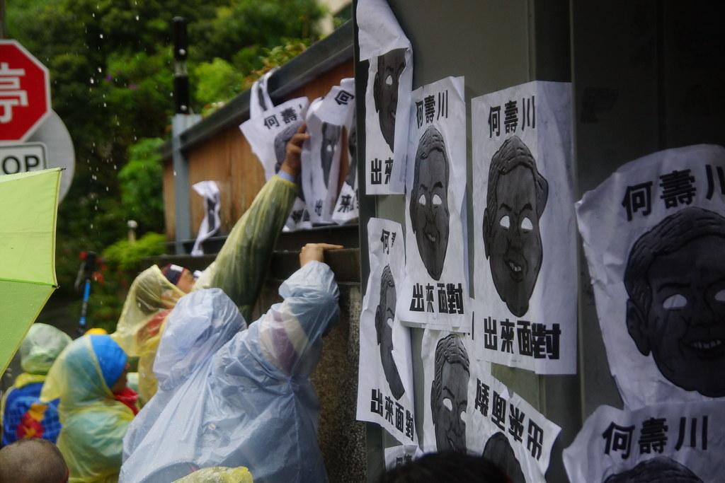 由於無人出面回應,Hydis工人們將印有何壽川臉孔的標語挑滿住宅圍牆。(攝影:王顥中)