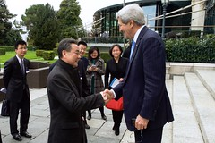 U.S. Secretary of State John Kerry greets Chinese Foreign Minister Wang Yi after they bumped into one another on March 29, 2015, in Lausanne, Switzerland, before a bilateral meeting on the sidelines of P5+1 partner negotiations about the future of Iran's nuclear program. [State Department Photo / Public Domain]