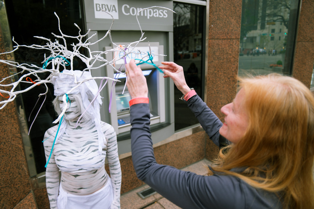 Carol Garfield Ties a Ribbon on the SyncYourInk.club Tree of Giving