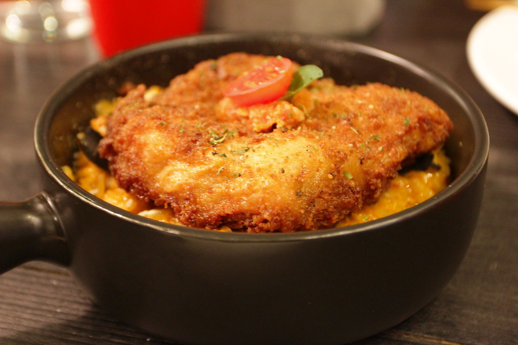 豪華肉醬雞排燉飯,上頭有一塊炸雞排,底下則是濃稠的肉醬飯....