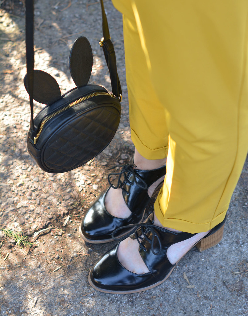 Yellow trousers with black rabbit-ears bag and cut out shoes