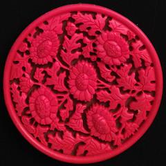 dishware(0.0), plate(0.0), produce(0.0), pink(0.0), art(1.0), pattern(1.0), flower(1.0), red(1.0), doily(1.0), circle(1.0), petal(1.0),