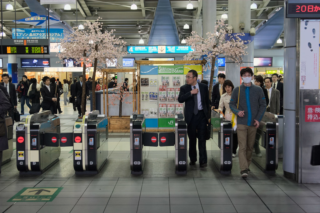 Commuters exit a subway line in Shinagawa Station in Tokyo, Japan