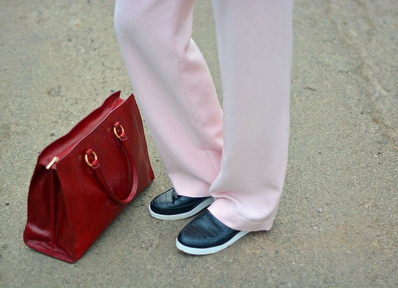 Pastel pink trousers, black slip on sneakers, cherry red tote