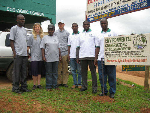 Group photo with all wearing Eco-Agric shirts standing by Eco-Agric Uganda signs