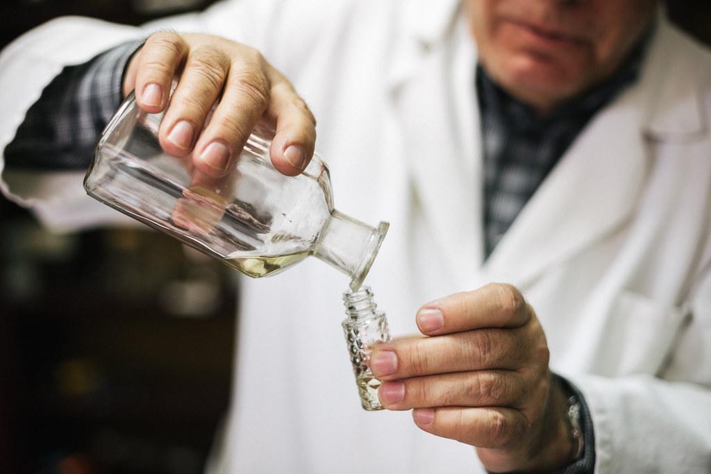 Gospodin Nenad Jovanov presipa miris iz velike u manju staklenu bocu za mušterije