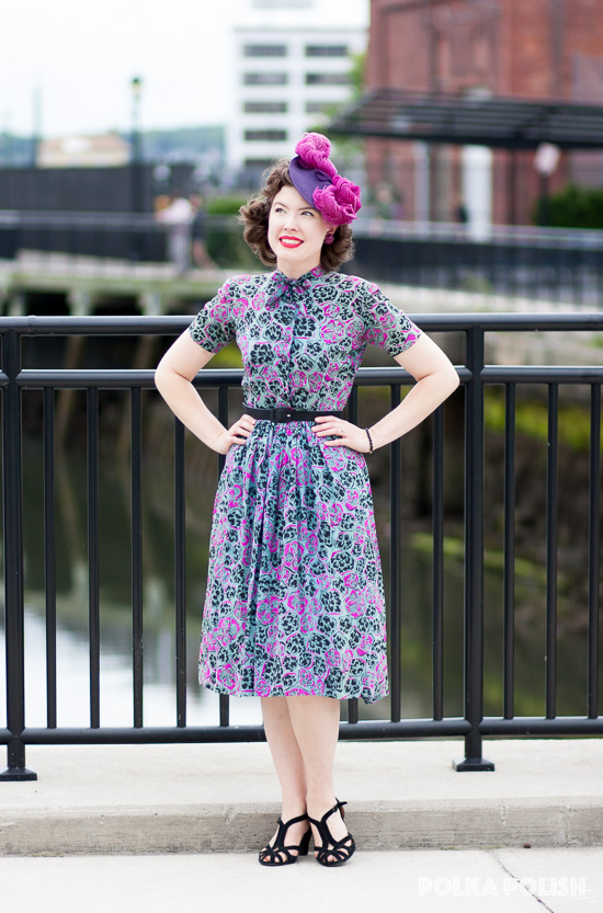 A colorful 1940s look, featuring a novelty print rayon dress and a purple tilt hat piled high with plumes. Black and bright magenta help tie it all together.